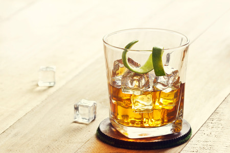 glass table: Glass of whiskey with ice on wooden background, warm color tone