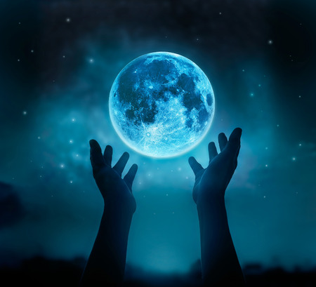 Abstract hands while praying at blue full moon with star in dark night sky background, Moon original image from NASA.gov