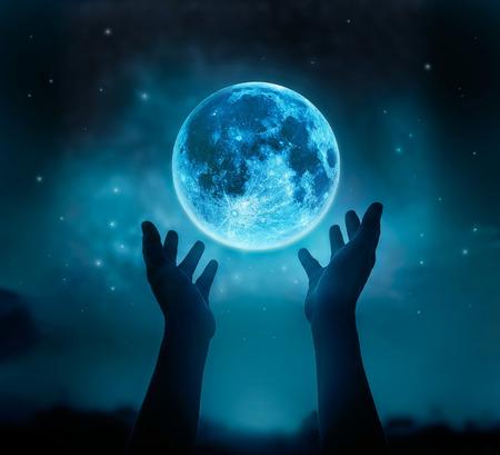 Abstrakte Hände beim Beten am blauen Vollmond mit Stern im dunklen Nachthimmel Hintergrund, Mond Original Bild von NASA.gov
