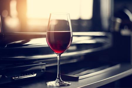 wijnglas in onderhoudende kamer bij zonsondergang vensterachtergrond