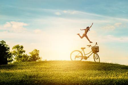 bicicleta: La mujer disfruta de sus vacaciones en el parque. Ella estaba saltando de alegría Foto de archivo
