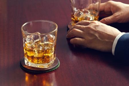 Whiskey auf Holztisch und Geschäftsmann mit Whisky in der Hand