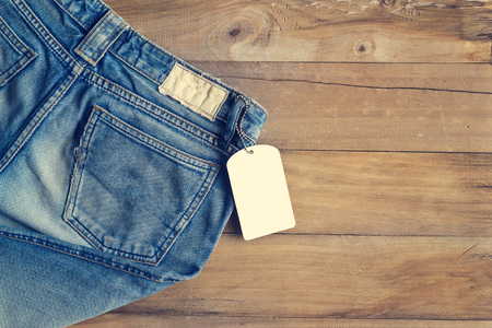 Blue jeans with white blank tag on wooden background