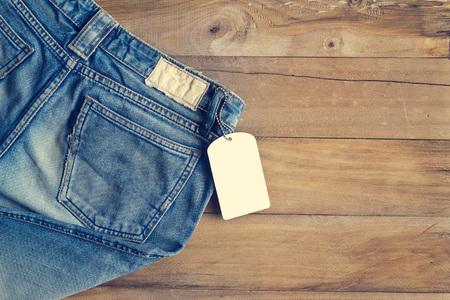 in jeans: los pantalones vaqueros azules con blanco etiqueta en blanco sobre fondo de madera Foto de archivo