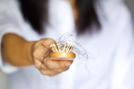 cabello: mujer que pierde el pelo en cepillo para el pelo en la mano, foco suave