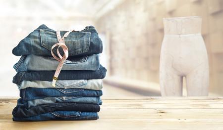 Jeans mit Maßnahme im Shop auf hölzernen Regal und unter der Mode Bekleidungsgeschäft