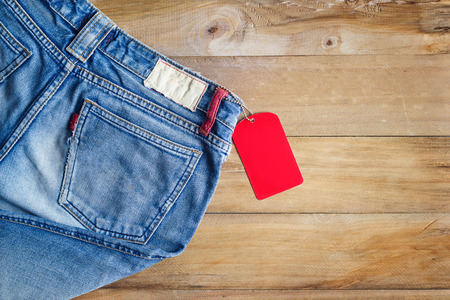 red jeans: Blue jeans with red blank tag on wooden background Stock Photo