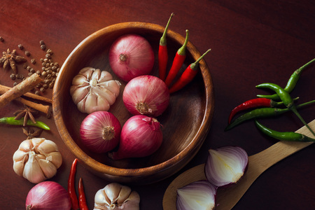 red pepper: Fresh herbs and spices, onion slices and garlic, and hot peppers scattered on wooden surface, spicy concept
