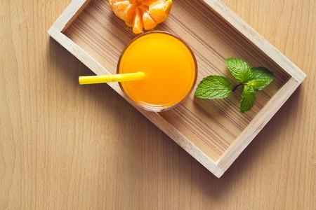 trompo de madera: Naranja y jugo de naranja con menta en bandeja de madera sobre fondo de madera, vista desde arriba Foto de archivo