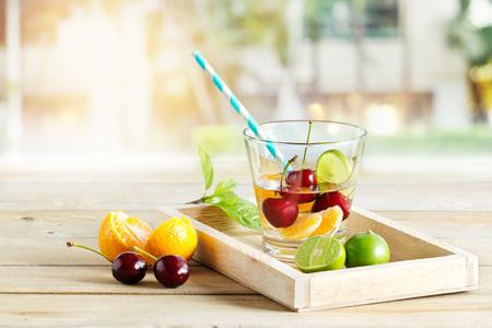 gesunde Entgiftung Wasser, Glas Kirsche, Orange und Kalk auf Tablett aus Holz Garten Hintergrund