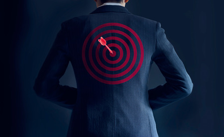 businessman get success with red arrow on target at the back of his suit on dark background, business concept