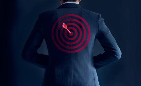 Unternehmer erhalten Erfolg mit roten Pfeil auf Ziel auf der Rückseite seines Anzugs auf dunklem Hintergrund, Business-Konzept Standard-Bild - 54938190