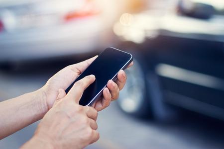 emergencia: mujer que usa smartphone en el borde de la carretera después de accidente de tráfico, enfoque suave