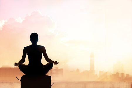 sitting meditation: Abstract woman meditating on pastel color tone city in the sunset Stock Photo