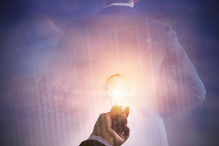 winning stock: business man holding light bulb on stock market investment trading and back of suit businessman on pastel color tone Stock Photo