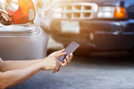 Człowiek za pomocą smartfona na poboczu drogi po wypadku drogowym Zdjęcie Seryjne