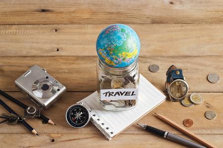 ahorro de dinero en un tarro de cristal en el fondo de madera, el concepto de viaje