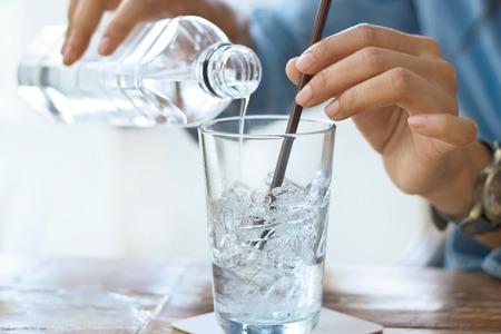 Femme boire de l'eau avec de la glace dans le verre sur une table en arrière-plan de restauration Banque d'images - 55377997