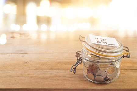 glass cup: Tip box, coin in the glass jar in cafe front of mirror at night Stock Photo