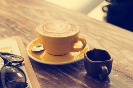 honey tone: Coffee cup and honey syrup in coffee shop on wooden table, Vintage color tone Stock Photo