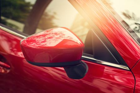 街の背景に側バックミラー赤い車 写真素材