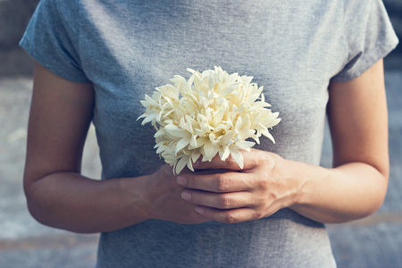 Praying woman with white bouquet in hands to show respect