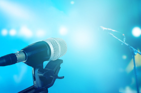 concert background: Microphone on stage with blue vibrant lighting concert background Stock Photo