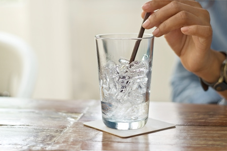 glass background: glass of water and ice in hand on table restaurant background