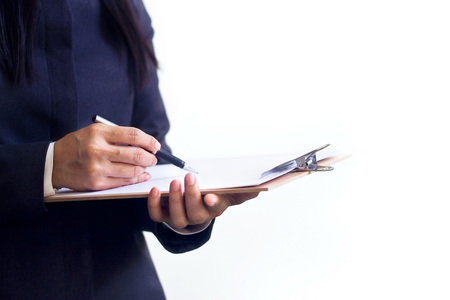 note pad: Businesswoman standing writing in planner on white baclground