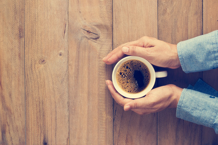 warm drink: Woman hands holding cup of coffee on wooden  background, Top view, Vintage tone