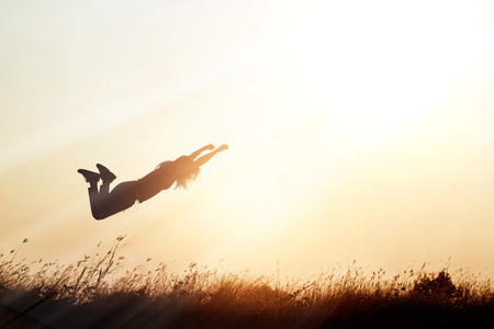 liberate: Woman flying over the meadow nature on sunset silhouette background, blank text