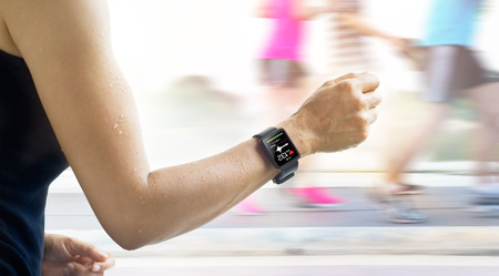 Running woman with smartwatch that show heart rate on the screen and people running background