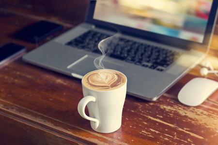 노트북, 마우스 및 커피 숍에서 오래 된 나무 테이블에 이어폰 커피 컵 스톡 콘텐츠