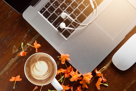 Laptop, earphone and flower with a cup of coffee on old wooden table everything for relaxing time Imagens - 61706417