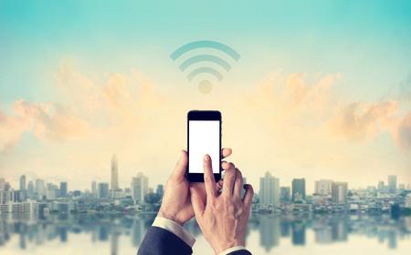 Uomo d'affari che collega lo smartphone Wifi rete in città