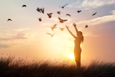 libertad: Mujer que ora y pájaro libre disfrutando de la naturaleza en el fondo la puesta del sol, el concepto de la esperanza Foto de archivo