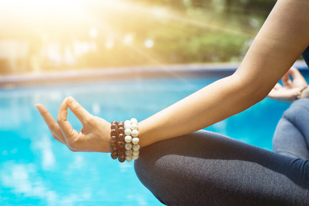 woman meditating with wrist beads in a lotus yoga position at blue swimming pool