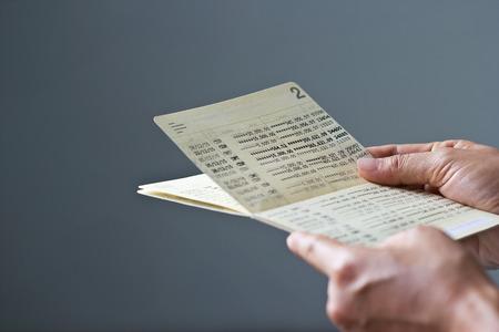 handen met spaarrekeningboek, boekbank op grijze achtergrond