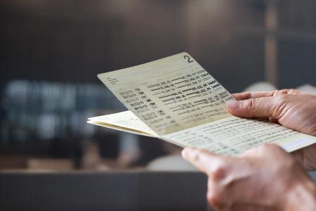 Manos sosteniendo la libreta de la cuenta de ahorro, banco del libro en un fondo de la oficina del banco Foto de archivo - 65036921