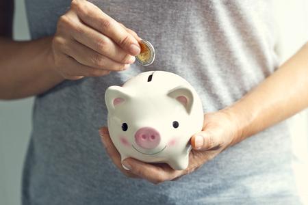coin bank: Woman hand putting coin into piggy bank