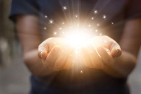 magia: Polvo de estrellas y la magia en manos de la mujer sobre fondo oscuro