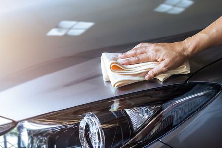 마이크로 화이버 천으로 깨끗한 스프레이로 자동차를 청소하는 여자
