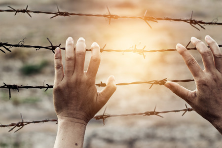 rusty wire: Woman hands touch a rusty wire imprison, Human rights violations concept