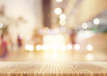 Wooden table in abstract blurred background of shopping mall lights