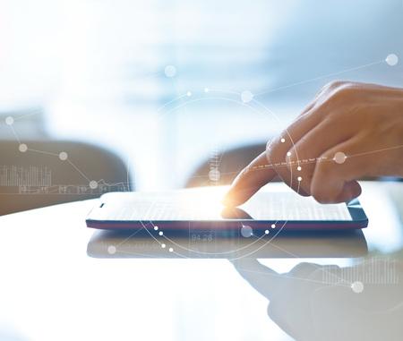 Hand van voorraadinzet met behulp van smartphone voor het controleren van de wereldwijde beurzen-interface op het scherm met grafische pictogrammen, zachte focus Stockfoto