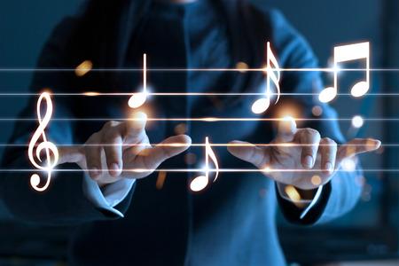 Frauenhände, die Musikanmerkungen über dunklen Hintergrund, Musikkonzept spielen Standard-Bild - 68993765