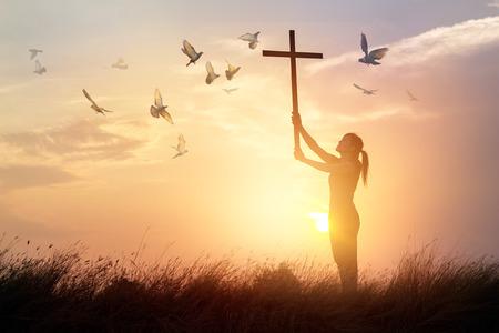 Vrouw die met dwars en vliegende vogel op de achtergrond van de aardzonsondergang, hoopconcept bidden