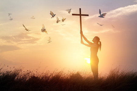 Woman praying with cross and flying bird in nature sunset background, hope concept Фото со стока