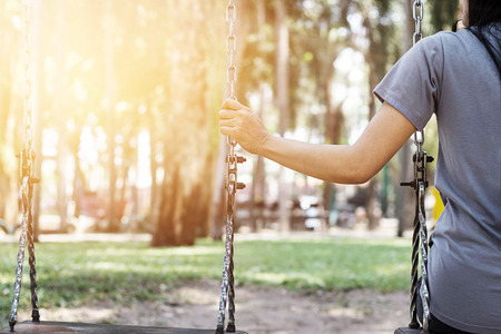 Lonely woman missing her boyfriend while swinging in the park villa in the morning Stock Photo