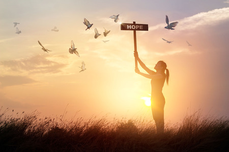 Woman holds a sign with word hope above head while chanting and praying, and flying birds on sunset background Stock Photo